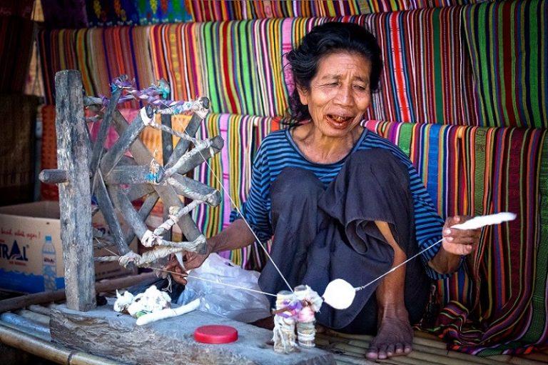 Sasak old woman traditionally makes yarn with a spindle wheel at traditional Sasak Sade Village, Lombok, West Nusa Tenggara, Indonesia